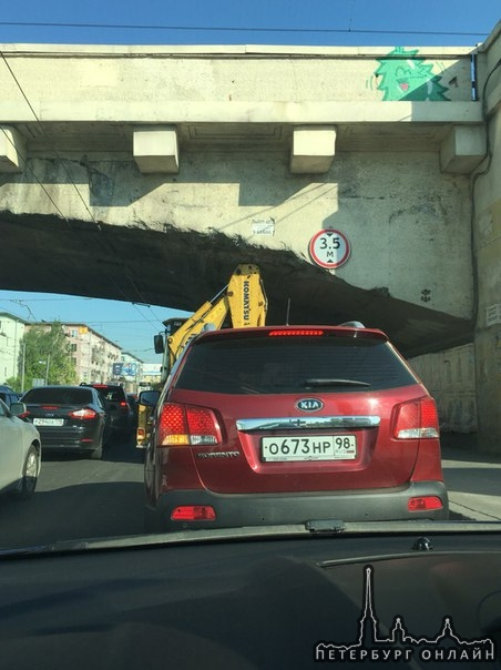 Трактор не пролез по высоте под железнодорожным мостом на Дальневосточном проспекте, перед поворотом...